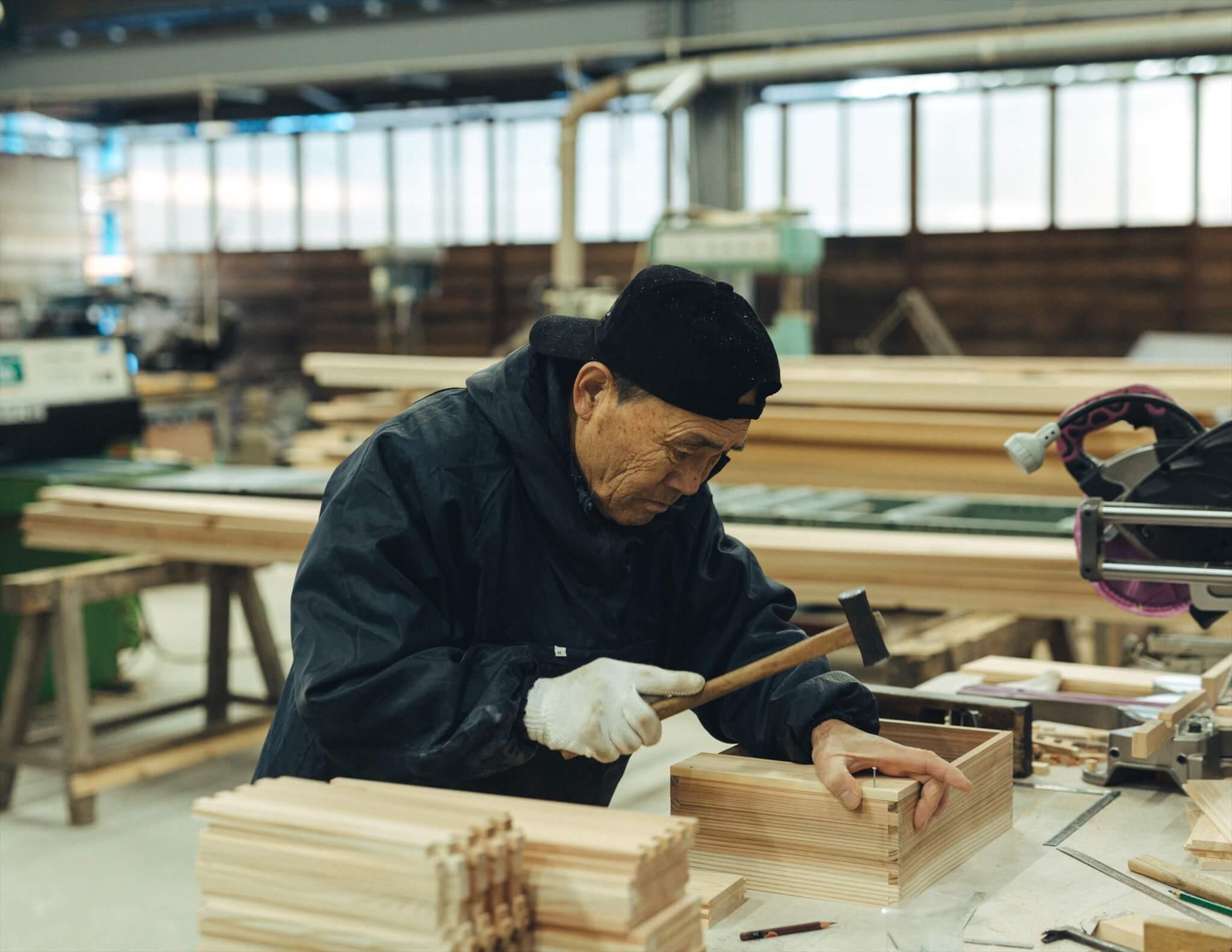 釘を打って木箱の底板を取り付ける大工さん