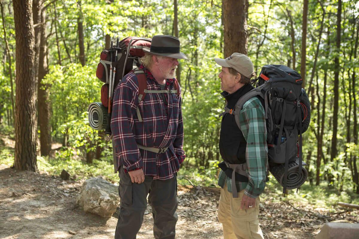 映画『ロング・トレイル』のワンシーン。森林の中で話し合う主人公のビルと悪友のカッツ