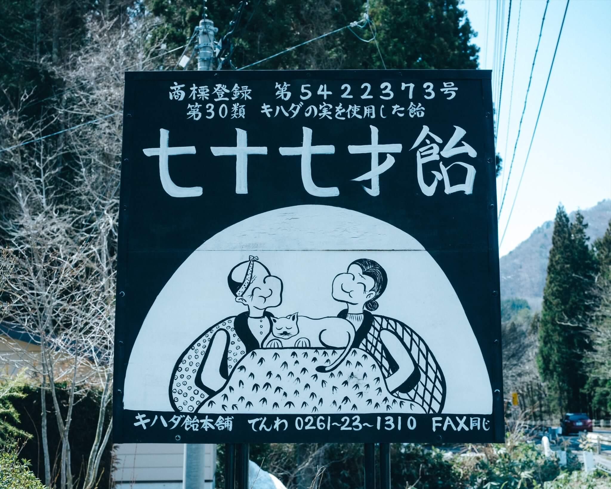 のっぺ山荘前にある看板。古川夫妻が67歳のとき、「あと10年はキハダ飴をつくる」という思いを込めて「七十七才飴」と名付けた