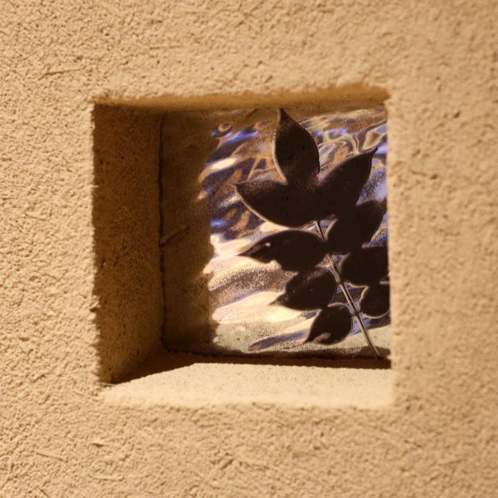土壁に埋め込まれたガラス。葉っぱのモチーフが印象的